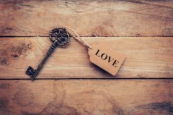 Oude sleutel vintage en tag voor tekst LOVE op houten achtergrond.