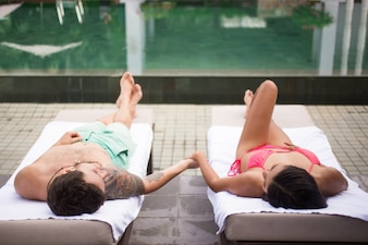 Paar Holding Hands and Resting Near Pool