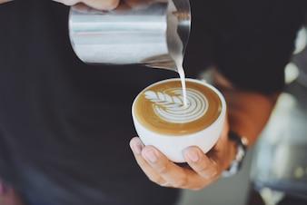 Persoon in dienst van een kopje koffie met een metalen kruik