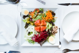 Plaat van salade met verse groenten, hardgekookt ei, tonijn en groene olijven.