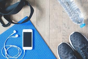 Platte lay-out van de mobiele telefoon met koptelefoon en sport apparatuur op houten achtergrond. Workout- en fitnessartikelen, bovenaanzicht