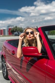 Portret van mooie sexy mode vrouw model in zonnebril zitten in luxe rode cabriolet auto met zee en hemel achtergrond. Jonge vrouw rijden op wegreis op zonnige zomerdag. Zee en lucht. Rode cabrio.
