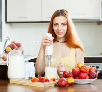 Positieve vrouw die drankjes maakt met nectarines en melk