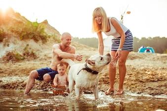 """""""Familie ontspannen op de kust met hond"""""""