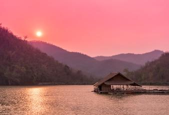 Raft drijvend op de rivier na zonsondergang tijd