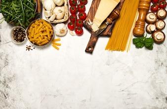 Rauwe pasta met tomaten en kruiden op een witte lijst