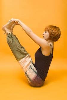 Rode meid die yoga asana uitoefent