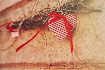Rood ornament in de vorm van een hart dat op een tak hangt