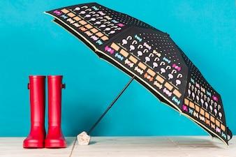 Rood water laarzen naast een open paraplu