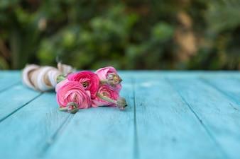 Roze bloemen op blauwe houten planken