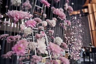 Roze chrysanten hangen op draadjes van het plafond in de avondhal