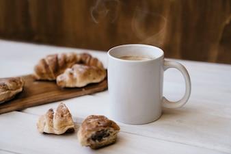 Samenstelling met croissants en koffiemok