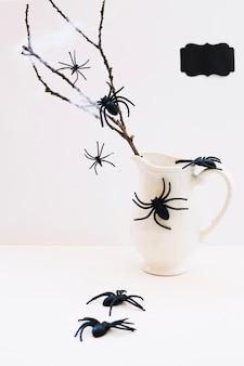 Samenstelling van spinnen en kruik met tak