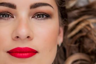 Schoonheid Vrouw Portret. Professionele make-up voor Brunette met groene ogen - Rode Lippenstift, Smoky Eyes. Mooi Mode Model Meisje. Perfecte huid. Bedenken. Geïsoleerd op een witte achtergrond. Een deel van het gezicht