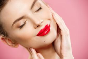 Schoonheidsconcept - Close-up Gorgeous Young Brunette Woman Face Portrait. Beauty Model Meisje met lichte wenkbrauwen, perfecte make-up, rode lippen, aanraken van haar gezicht. Geïsoleerd op roze achtergrond