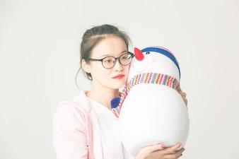 Shot in de studio van de jonge Aziatische vrouw met een kerstman sneeuwpop