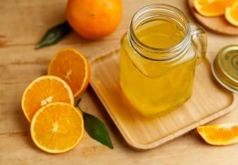 Sinaasappelsap en sinaasappelen op retro houten bureau