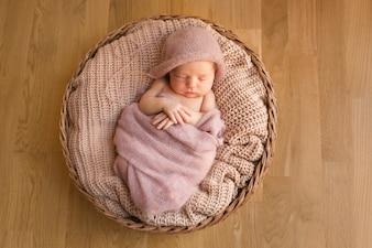 Slapende baby met de handen gekruist op de buik