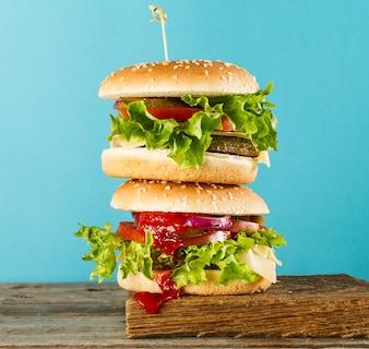 Smakelijke ongezonde hamburgers op houten bord op blauwe heldere achtergrond, klaar om te eten of te serveren. Heldere achtergrond. Selectieve focus.