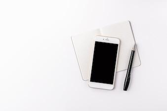 Smartphone mockup notitieblok bovenaanzicht wit bureau