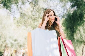 Smiley vrouw met telefoon na het winkelen