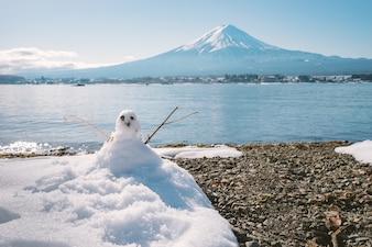 Sneeuwpop staande in de winter landschap op Fuji Moutain achtergrond bij Kawaguchiko Lake, Japan