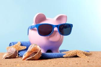 Spaarvarken op een strand met zonnebril