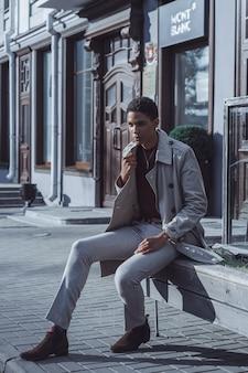 Stijlvolle jonge Afro-Amerikaanse man poseren in een straat cafe