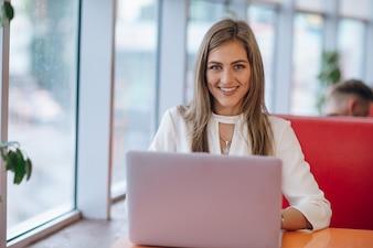 Stijlvolle vrouw met smiley gezicht met een laptop op de voorgrond