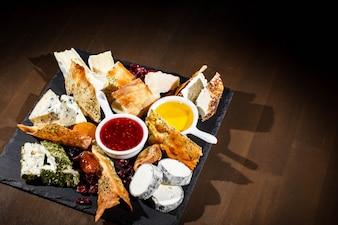 Stukken camembert, blauwe kaas, cheddar liggen op zwarte plaat met sausjes in witte kommen