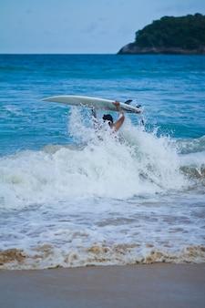 Surfer met surfplank op strand