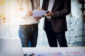 Teamwork proces. Jonge zakenmanagers die werken met een nieuw opstartproject. Labtop op kantoor houten tafel, toetsenbord typen, sms-bericht, grafiekplannen analyseren