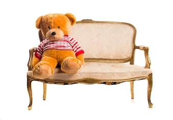 Teddy zittend op vintage leunstoel