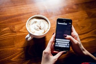 Telefoon houten beker hete koffie