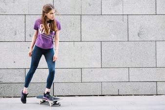 Tiener meisje die een skateboard rijdt