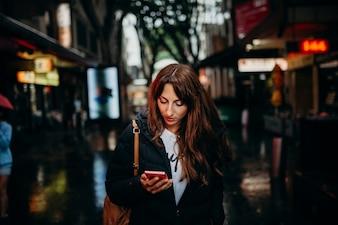 Toeristisch zoeken naar restaurant met mobiele telefoon in de buurt van Chinatown in Sydney, Australië.