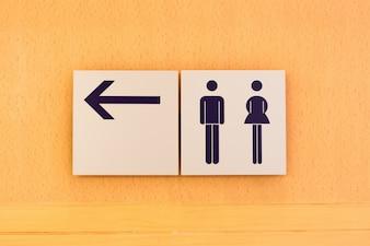 Toilet teken en richting op houten achtergrond