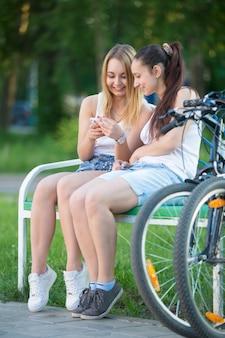 Twee meisjes in een bank te kijken naar hun telefoon