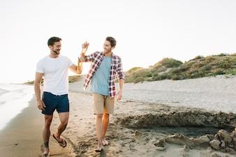 Twee vrienden lopen op het strand