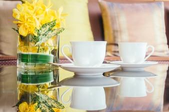 Vaas bloem en witte koffiekop op tafel en kussen op de bank