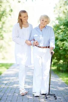 Verpleegster die hogere vrouw met wandelstok