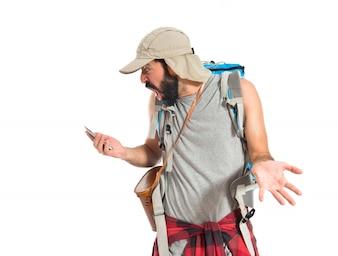 Verrast backpacker praten met mobiele over witte achtergrond