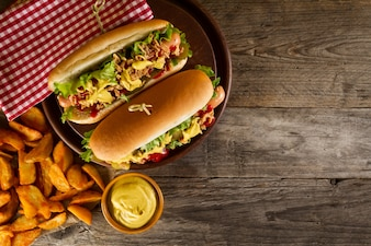 Verscheidenheid van klassieke traditionele Amerikaanse smakelijke junk ongezond eten op houten achtergrond met kopie ruimte. Hotdogs en Chips.