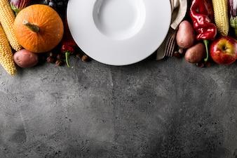 Verschillende seizoensgebonden herfst groenten en fruit met lege plaat op grijze achtergrond