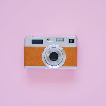 Vintage camera kijken op roze achtergrond, minimale stijl