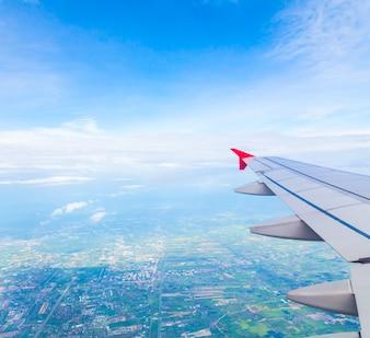 Vleugel van een vliegtuig met een stad achtergrond