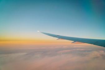 Vleugel van een vliegtuig vliegt boven de wolken