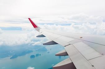 Vleugel van een vliegtuig vliegt boven de zee en het eiland