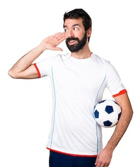 Voetballer met een voetbal bal iets te luisteren