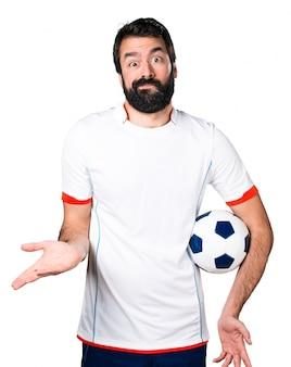 Voetballer met een voetbal die onbelangrijk gebaar maakt